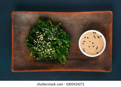 Delicious Japanese cuisine, wakame chuka salad with spicy sauce served on authentic square clay plate, close up. Healthy vegetarian seafood