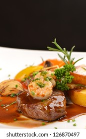Delicious juicy barbecued steak and prawns with grilled tomato and roasted potatoes. Surf and Turf style. Shallow dof
