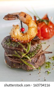 Delicious juicy barbecued steak and prawns with grilled tomato. Surf and Turf style.