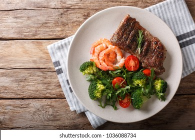Delicious juicy barbequed steak and prawns with vegetable salad closeup on the plate. Surf and Turf style. horizontal top view from above