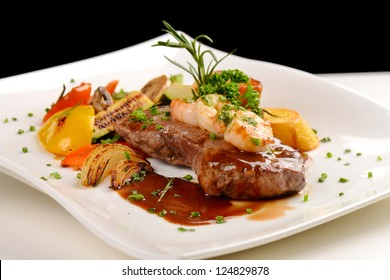 Delicious juicy barbequed steak and prawns with grilled tomato and roasted potatoes. Surf and Turf style. Shallow dof