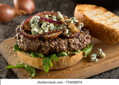 A delicious juicy burger with blue cheese, arugula, sauteed red onions and muchrooms.