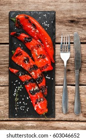 Delicious and juicy grilled paprika served on black slate with knife and fork, on rustic wooden table, top view. Restaurant menu photo.
