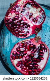 delicious, juicy pomegranate on a blue handmade ceramics plate