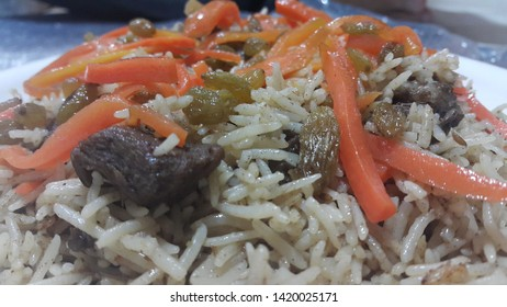 Delicious Kabuli pulao from Basmati Rice: Home made pulav with beef, carrot and dried grapes or kishmish or raisin served in a white plate