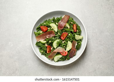 Delicious kale salad on grey table, top view