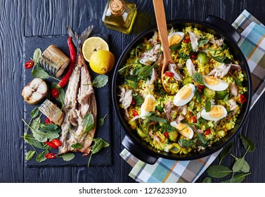 delicious Kedgeree with flaked smoked fish, hard boiled eggs, rice, kale, brussel sprouts, spices and herbs in a dutch oven on a black wooden table with ingredients, view from above, flatlay