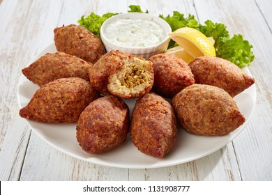 delicious kibbeh stuffed with fried beef ragout and pine nuts served on a white plate with lettuce and lemon slices on old wooden table, classic lebanese recipe, horizontal view from above, close-up