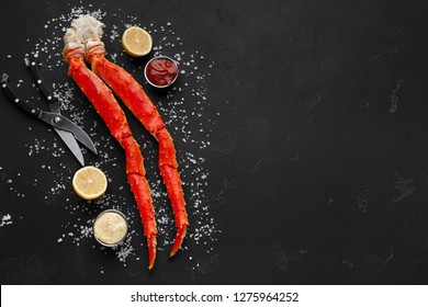 Delicious king crab legs with cutting scissors and sauces on black background, top view, copy space