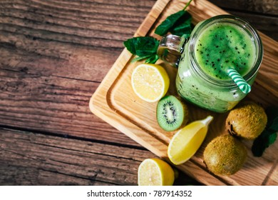 Delicious kiwi smoothie with mint in mason jar on table against dark wooden background. Healthy lifestyle concept. Top view