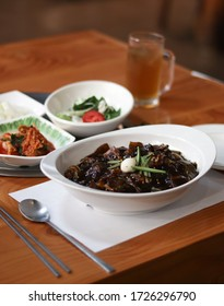 Delicious Korean black bean sauce jajangmyeon noodle set with kimchi and Korean pickle background in white bowl on wooden table. This sweet and savory noodle dish is popular. Selective focus.