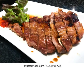 Delicious Kurobuta Pork Steak Grilled with Soy Sauce and organic vegetable salad decorated in white dish on the black table.