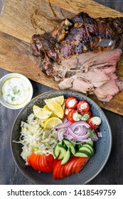 Delicious Lamb leg roast cooked on a rotisserie served with fresh greek salad and sauce for souvlaki wraps.