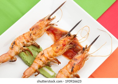 Delicious large spicy grilled whole shrimps -scampi- with salsa and guacamole sauces and fresh cilantro.