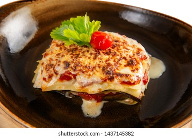 Delicious lasagne bolognese with mushrooms parmesan cheese in a brown cup isolated on white background