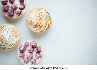 Delicious lemon and raspberry tartlets with meringue on a white vintage plate. Sweet treat on a light blue background. Flat lay and copy space. Top view