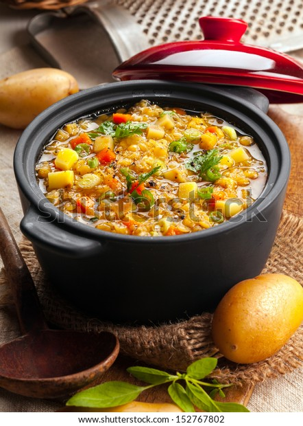 Delicious lentil and vegetable stew in a rustic kitchen in an open crock, high angle view