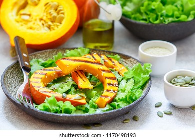 Delicious light salad of grilled pumpkin slices and lettuce with sesame seeds, lemon juice and olive oil. Healthy diet, vegetarian snack. Selective focus