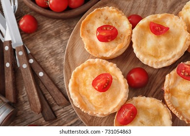 Delicious little meat pies on wooden board