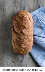 Delicious loaf of artisan sourdough bread on rustic wood bench with blue cloth, top view, copy space
