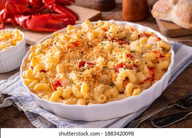 A delicious lobster macaroni and cheese casserole on a rustic wood table top.