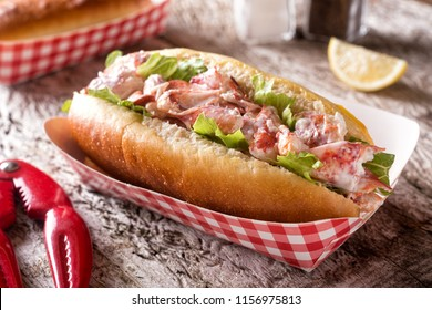 A delicious lobster roll on a rustic wood table top.