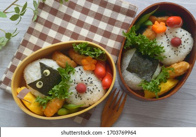 a delicious -looking bento box consists of rice balls, sausage, chicken nugget, pickled plum and the assortment of vegetable