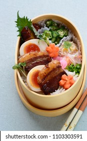 a delicious looking bento consists of braised pork belly, boiled eggs, steamed rice and the assortment of vegetables