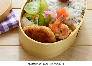 a delicious looking bento consists of rice, shrimp, burdock root, potato, carrot, grapes with the assortment of vegetables