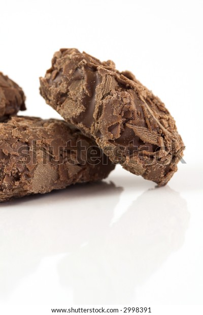 Delicious looking chocolate truffles on white background