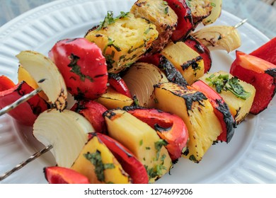 A delicious looking grilled vegan kabob. Kabob has tempeh, red bell peppers, onions, pineapple, flaked with cilantro.