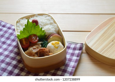 a delicious looking lunch box (bento) consists of tofu dregs salad, ginger pork, tomato, sweet potato and steamed rice