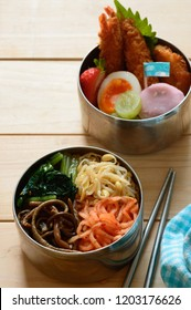 a delicious looking lunch box consists of bibimbap (Korean mixed rice). fried shrimp, boiled egg, and sweet Japanese dumplings