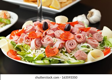 A delicious looking tossed chefs salad or antipasto with meat cheese and kalamata olives.