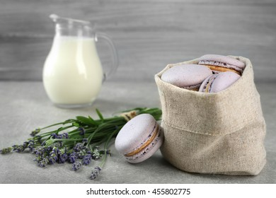 Delicious macaroons, milk and lavender on table