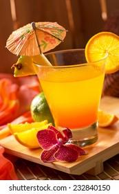 A delicious mai tai cocktail in a tropical tiki hut setting.