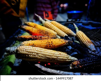 Delicious maize is being sold on the street of Varanasi in India during rainy season. Roasted and baked maizes for sale. Maize is hanging in the shop for sale.
