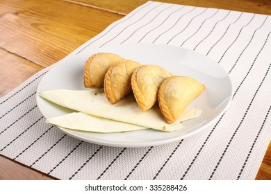 delicious Malaysian curry puff served on white plate on wood background
