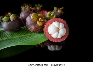 Delicious mangosteen fruit , flesh mangosteen and cross section showing the thick purple skin and white flesh of the queen of friuts, with leaf on dark background with select focus.