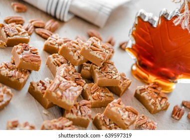 Delicious maple fudge with pecan and maple syrup on the  background
