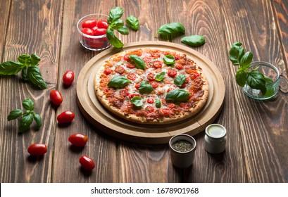 Délicieuse pizza margherita avec tomates et basilic sur bois.