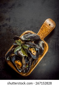 Delicious marinated boiled mussels in a wooden dish garnished with bay leaves and seasoned with spices, overhead view