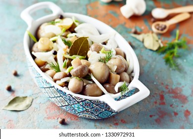 Delicious marinated mushrooms in a beautiful bowl with onions, pepper, dill and olive oil on a gray-blue background, top view, champignons