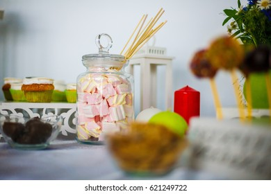 A delicious marshmallow in a jar on the table with other sweet desserts for a feast.