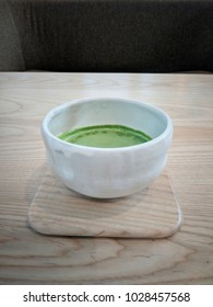 Delicious matcha milk tea in japanese style tea cup. Milky green matcha latte in a japanese ceramic bolw placed on a white wood table.