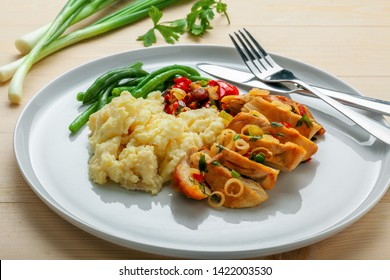Delicious meal made of chicken fillet, green beans, mashed potato and vegetable sauce on a wooden table.