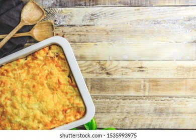 Delicious meat casserole with eggplant, minced meat, tomato, bechamel sauce and cheese. Greek moussaka on rustic wooden background. Top view