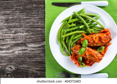 Delicious Meat Cutlets stewed with onion, carrot tomato sauce, decorated with basil leaves in a white dish with boiled green bean on a table napkin with fork and knife, top view