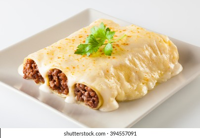 Delicious meat filled pasta on a plate. Italian cannelloni, Spanish canelones.