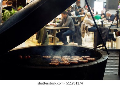 delicious meat grilling with flames and smoke. catering in food court at mall. space for text. open kitchen